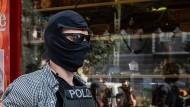 Ein Beamter der Polizei mit sichergestellten Gegenständen nach einer Razzia in einer Wohnung eines Mitglieds einer arabischen Großfamilie.