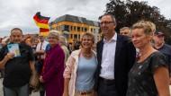 AfD-Spitzenkandidat Jörg Urban posiert mit zwei Anhängerinnen am 15. August vor einem Wahlkampfstand in Bautzen.