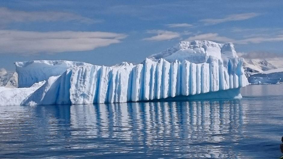 Eis kennt viele Formen: die Spiegelungen der Felswände erscheinen wie eine Parade grauer Hochhäuser unter Wasser.