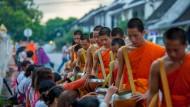 Die Speisung der himmlischen Bettler: Jeden Morgen bei Sonnenaufgang sammeln sich die buddhistischen Mönche in Luang Prabang zu ihrem Almosengang.