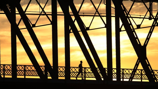 A jogger runs across the Hawthorne Bridge at sunrise Thursday, June 28, 2012...