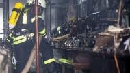 Zerstört: Feuerwehrmann vor einem Regal mit geschmolzenen Schallplatten in Geisenheim