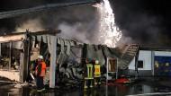 Abgebrannt: Feuerwehrleute vor dem Supermarkt in Schlüchtern, der zum Raub der Flammen geworden ist