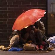 Süchtig: Abhängige konsumieren  im Bahnhofsviertel unter einem Regenschirm Drogen.