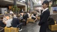 Vorbild: Eine Flugbegleiterin posiert in einem historischen Kostüm, während Bewerberinnen und Bewerber auf das Casting warten