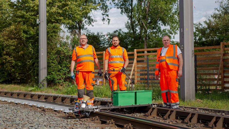 Die Weißmacher: Die VGF-Mitarbeiter Dieter Lach, Nicola Heimbücher und Kurt Landau (von links) haben eine leichte Lackiermaschine für Schienen gebaut.