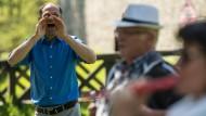 """Auf Zuruf: Der Initiator des Weltrekordversuchs, Roland Siegwald (links) von der """"Theatergruppe Mobile Albania"""" demonstriert, wie das mit den Rufen so funktionieren soll."""