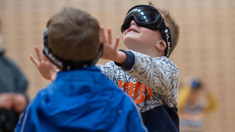 Herantasten an die Aufgabe: Kinder lernen, sich mit der lichtundurchlässigen Schutzbrille zu bewegen.