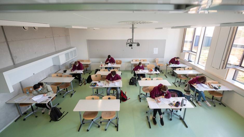 Besonderes Schuljahr: Schüler lesen mit Masken Prüfungsaufgaben durch.
