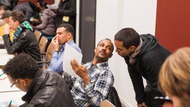 """Einsatz für Flüchtlinge: Ronjit Medda von """"Teachers on the road"""" (stehend) hilft einem Mann im IG-Metall-Haus beim Lernen der deutschen Sprache."""