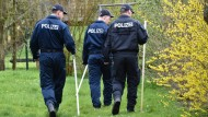 Bereitschaftspolizisten laufen am Dienstag einen Garten in Wanfried ab.