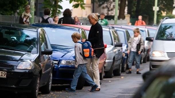 Mit dem Auto zur Schule - viele Eltern bringen ihre Kinder mit dem Auto zur Schule, trotz Aktion der Stadt Wir laufen zur Schule, die ökologische Aspekte und die Sicherheit mitberücksichtigt.
