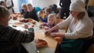 Stich für Stich: Kristel Neitsov-Mauer hilft ihrer Tochter, traditionelle Lederschuhe in der Estnischen Sonntagsschule zu basteln.