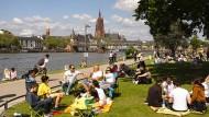 Lockerungsübungen: Familien, Paare, Solisten und Freizeitsportler am Frankfurter Mainufer.