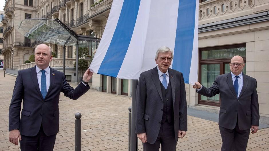 Flagge zeigen: Anlässlich antisemitischer Vorfälle hissen Ministerpräsident  Volker Bouffier, Uwe Becker (links) sowie Jakob Gutmark (r) vom Landesverband der hessischen Jüdischen Gemeinden vor der Staatskanzlei die Flagge des Staates Israel.
