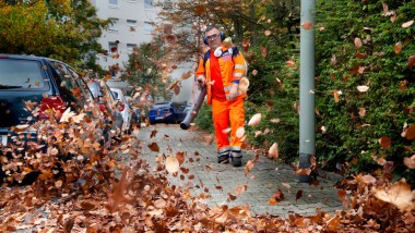 Kraftvoll: Ein FES-Mitarbeiter bläst in Frankfurt Laub von einem Fußweg.