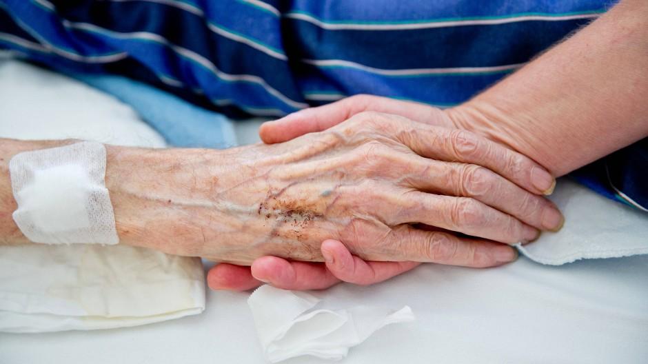 Nicht allein: Eine Krankenpflegerin der Onkologie hält die Hand eines Patienten.