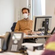 Sicher ist sicher: Wenn nicht immer genug Abstand gehalten werden kann, empfiehlt es sich, die Maske auch im Büro zu tragen.