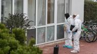 Ermittler der Spurensicherung untersuchen die Einschusslöcher in den Fenstern der Flüchtlingsunterkunft in Dreieich-Dreieichenhain.