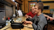 Sitzt gerne am Computer: Julien Eyres, der die Maus auch mit der linken Hand bedienen kann, mit seinem Vater William