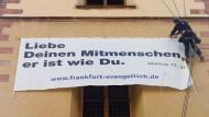 Mahnung: Ein Spezialist bringt das Banner mit einem Spruch Jesu am Turm der St. Katharinenkirche an.