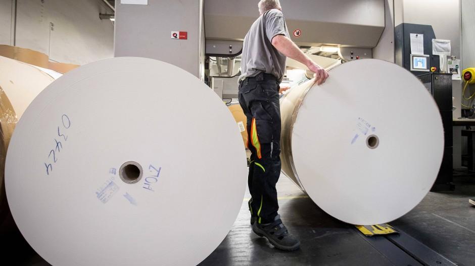 Knappes Gut:  Ein Drucker wechselt Papierrollen für den Buchdruck in einer Druckmaschine in der Druckerei CPI Clausen & Bosse.