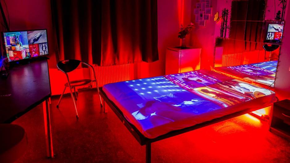"""Spielplatz: Auf dem Bett der Prostituierten """"Lora"""" präsentiert Ulrich Mattner 500 Fotos aus dem Bahnhofsviertel."""