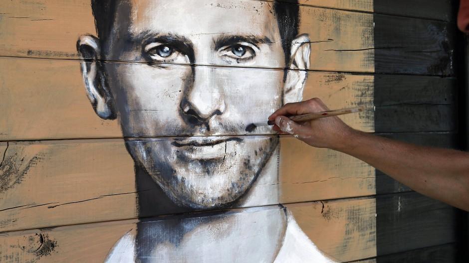 Ein Künstler malt das Porträt von Novak Djokovic in Serbien auf eine Wand.