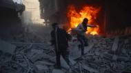 Anwohner fliehen in Damaskus vor einem in den Trümmern brennenden Fahrzeug