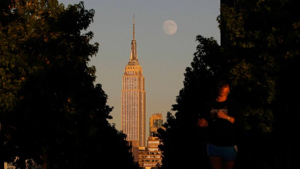 The moon rises at sunset behind New York's Empire State building as a woman runs along a promenade in Hoboken, New Jersey