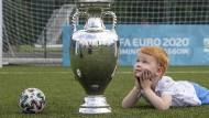 Ein Junge in Glasgow mit dem Pokal, den er Europameister bekommt.