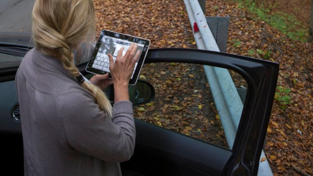 Woman checks tablet for direction, at roadside