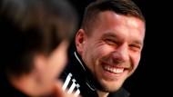 Der Strahlemann: Lukas Podolski wird als ein Spieler in Erinnerung bleiben, der fast immer ein Lächeln zeigte. Das war auch am Dienstag bei seiner letzten Pressekonferenz mit Bundestrainer Löw (links) im Kreis des Nationalteams nicht anders.