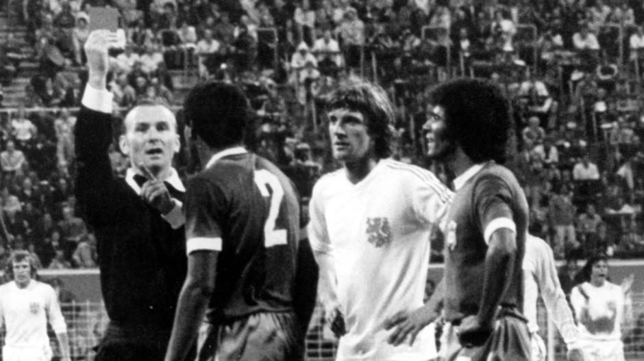 Der Fußball bekommt eine gemeinsame Sprache: Kurt Tschenscher zeigt dem brasilianischen Abwehrspieler Luis Pereira (2.v.l) 1974 wegen Foulspiels die Rote Karte.