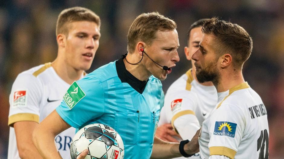 Diskussionsbedarf auf dem Platz und danach: Schiedsrichter Martin Petersen umringt von Wiesbadener Spielern
