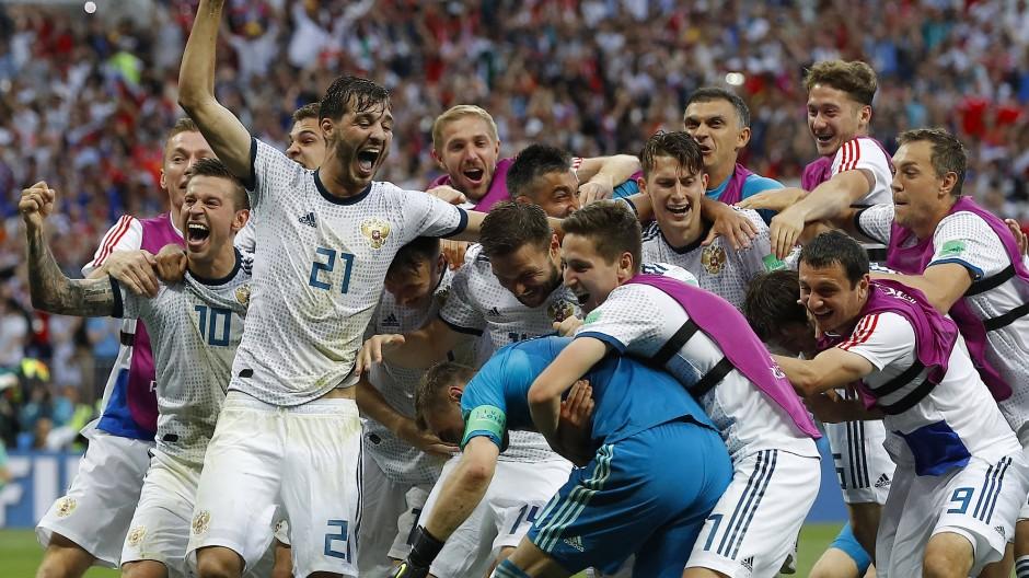 Alle auf einen: Die russischen Spieler wissen ganz genau, wem sie die große Überraschung zu verdanken haben: ihrem Torhüter Igor Akinfeew.