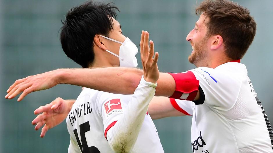 Kompliment vom Kapitän: Eintracht-Spielführer Abraham (rechts) gratuliert dem Frankfurter Siegtorschützen Kamada.