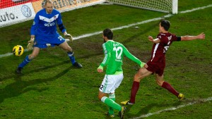 Bas Dost of Germany's first division Bundesliga club VfL Wolfsburg scores his team's first goal against goalkeeper Robert Wulnikowski of third division club Kickers Offenbach during their German soccer cup, DFB Pokal, quarter final match in Offenbach
