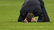 Tottenham-Trainer Mauricio Pochettino kann sein Glück kaum fassen und sinkt im Anzug auf den Rasen.
