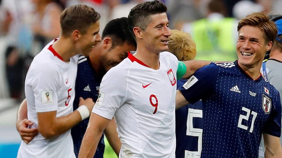 Polens Robert Lewandowski (Mitte) und Japans Gotoku Sakai (rechts) nach dem Spiel.