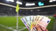 Geldscheine liegen im Fußball zwar nicht auf dem Rasen, spielen aber doch irgendwie mit.