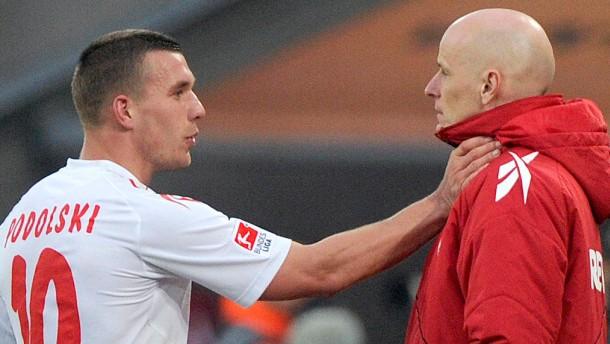 Podolski (links) zeigt seinem Trainer Solbakken, was er getan haben soll - es gab Rot und eine Sperr