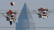 Techniker warten in Frankfurt Stromleitungen an Hochspannungsmasten.