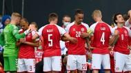 Die dänischen Fußballer bilden einen Kreis um ihren Mitspieler