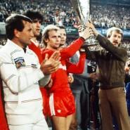 """Und sie suchen den Pokal: Bei der abendlichen Feier """"entführt"""" Bernd Hölzenbein (links neben Pokalträger Bruno Pezzey) die Trophäe."""