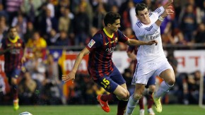 Barcelona's Bartra battles for the ball against Real Madrid's Bale during their King's Cup final soccer match at Mestalla stadium in Valencia
