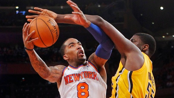 New York Knicks' Smith drives over Indiana Pacers' Hibbert to score in Game 1 of their NBA Eastern Conference Semi-finals basketball playoff series in New York