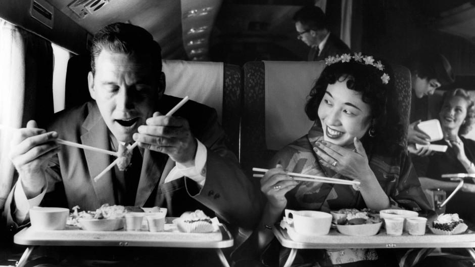 Clash of Cultures: Ein Passagier von Northwest Airlines versucht in den sechziger Jahren mehr oder weniger verzweifelt, mit Stäbchen zu essen.