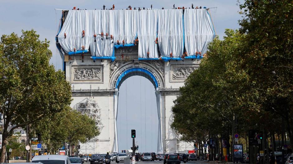 Ein einzigartiger Anblick: Arbeiter entrollen silber-blaue Stoffbahnen und verhüllen damit den Triumphbogen in Paris.