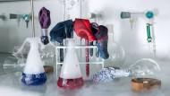 Einstecktücher der Marken Braska, Hackett, Hermès, Boss und Olymp in verschiedenen Rundkolben und Reagenzgläsern im Labor der anorganischen Chemie am Campus Riedberg der Goethe-Universität.